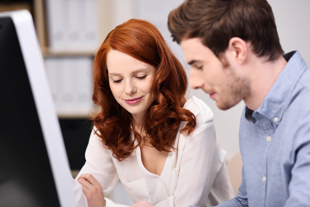 Attractive young man and woman working together sitting at a desk with a desktop computer reading paperwork together with a smile