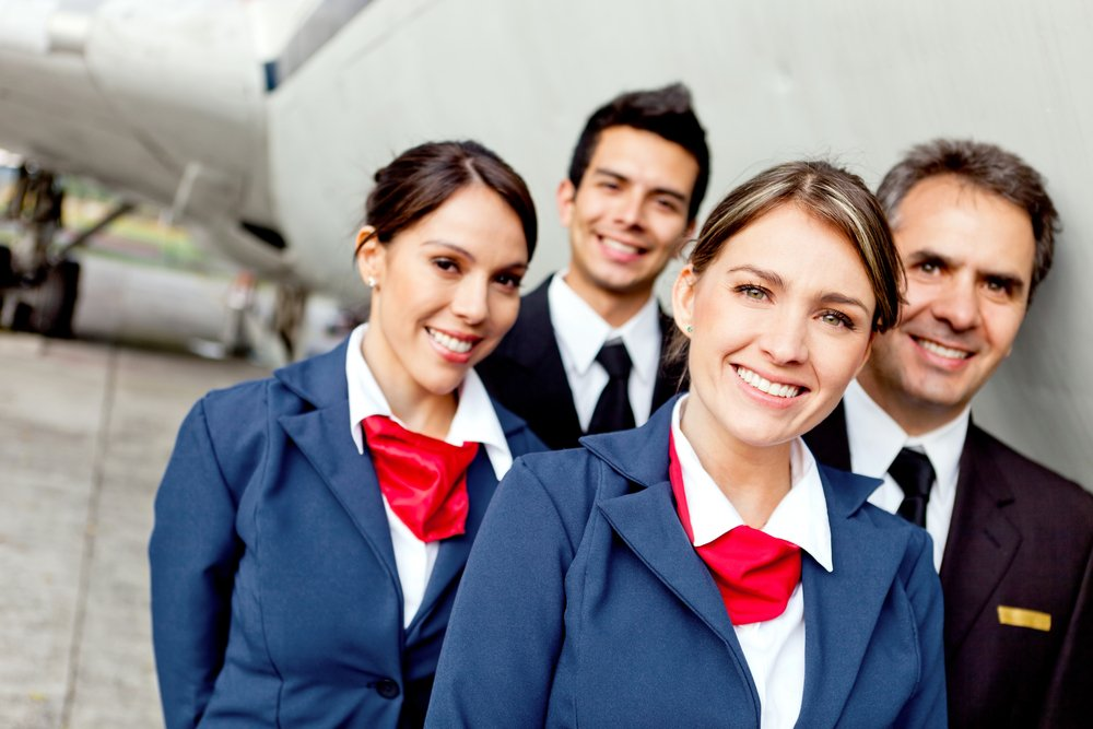 Cabin crew team with pilots and flight attendants smiling