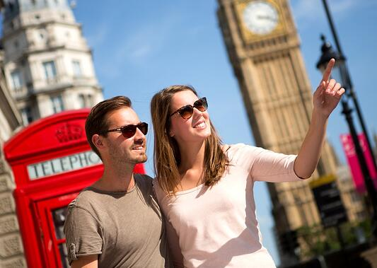 Couple sightseeing in London pointing away near the Big Ben.jpeg