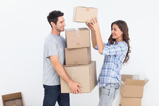 Happy woman giving boxes to her husband while they are moving.jpeg