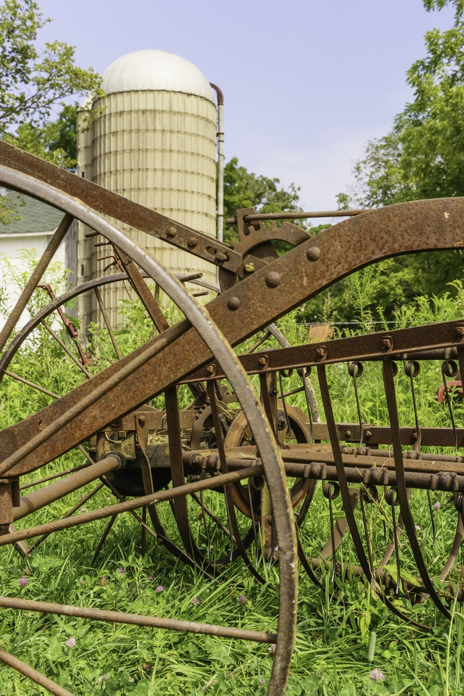 Rural bygones at a glance Vintage farm machinery stands rusting in grass near silo on public educational farm, summer in northern Illinois