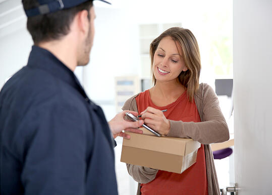 Woman sigining electronic receipt of delivered package-1
