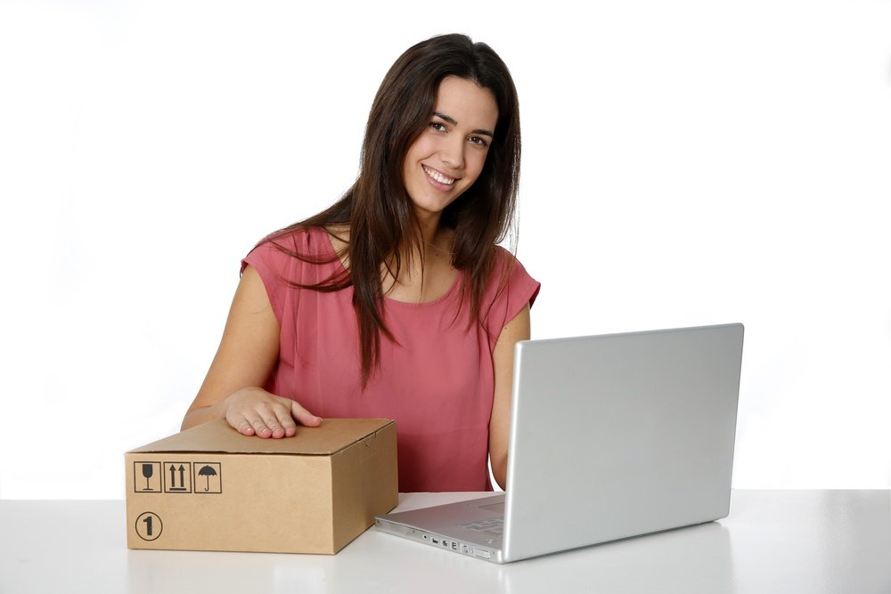 Young smiling woman preparing package to be sent by mail