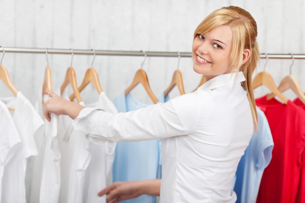 confident young woman choosing shirt in a shop